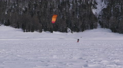 A snowkiter on a frozen lake in the Switzerland Alps Stock Footage