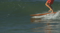 A male surfer riding a wave and doing a hang-5 trick on a longboard surfboard. Stock Footage