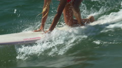 A female surfer riding a wave and wiping out on a longboard surfboard. Stock Footage