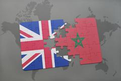 Puzzle with the national flag of great britain and moroccoon a world map back Stock Photos