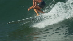 A male surfer rides a wave and wipes out on a longboard surfboard, slow motion. Stock Footage