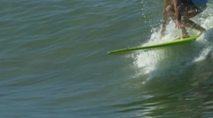 A male surfer rides a wave on a longboard surfboard, slow motion. Stock Footage