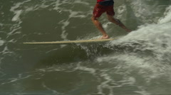 A male surfer riding a wave and doing a hang-5 trick on a longboard surfboard, s Stock Footage