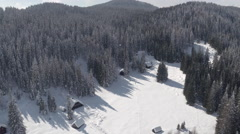 AERIAL: View of idyllic ski resort village surrounded by dense forest in winter Stock Footage