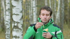 A young man in the autumn forest eating french fries. Warm jacket and beautiful Stock Footage