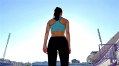 Track runner athlete woman girl running at stadium, sun flare, slow motion Stock Footage
