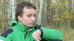 A man checks the messages on social networks on smart watches in the autumn park Stock Footage