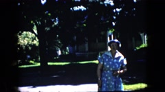 1969: an elderly woman wearing a dress and hat walks  Stock Footage