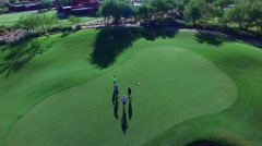 4K Aerial Drone Desert Golf Course Flyover 4 Men Putting Stock Footage
