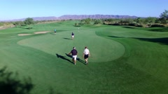 4K Aerial Drone Desert Golf Course Flyover 4 Men Walking to Green Stock Footage