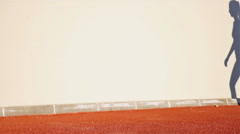 Track runner woman and her shadow on a wall preparing to run, slow motion Stock Footage