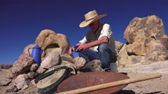 Cowboy sitting at the fire pit, wild west Stock Footage