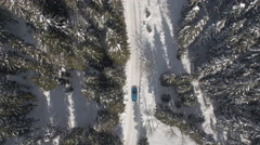 AERIAL: Car driving on plowed road among alpine cabins and huts in winter forest Stock Footage