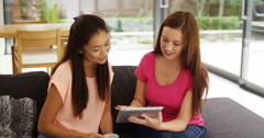 4k, Smiling young girls having fun with tablet in the living room. Stock Footage