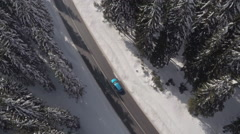 AERIAL: Blue automobile driving through stunning snowy pine forest in mountains Stock Footage