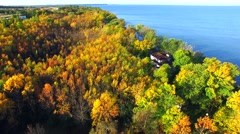 Scenic aerial flight over Autumn Trees and homes on rural Shoreline. Stock Footage