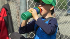 A boy drinks from a green water bottle at little league baseball practice. Stock Footage
