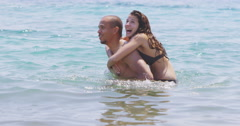 4K Happy couple on beach vacation, relaxing and having fun in the water Stock Footage