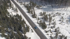 AERIAL: Car driving through stunning snowy spruce forest in winter wonderland Stock Footage