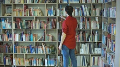 A male college student studies in the library Stock Footage