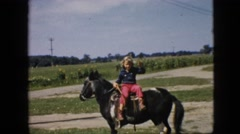 1957: cute girl sitting on black horse with tail field calling someone beautiful Stock Footage