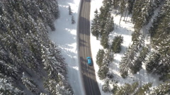 AERIAL: Cars driving through magical snowy spruce forest in winter wonderland Stock Footage