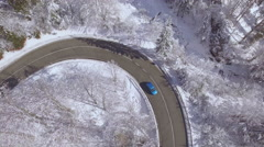 AERIAL: Blue car driving around sharp curve in magical snowy winter wonderland Stock Footage