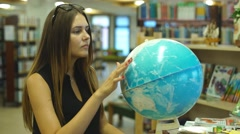 Female college student looking at a globe Stock Footage