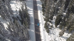 AERIAL: Car driving through magical snowy spruce forest in winter wonderland Stock Footage