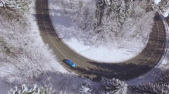AERIAL: Blue car driving around sharp bend in magical snowy winter wonderland Stock Footage