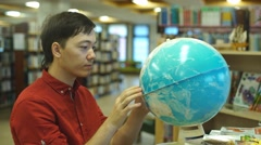 Male college student looking at a globe Stock Footage