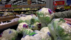 Motion of woman's hand picking cauliflower inside superstore Stock Footage
