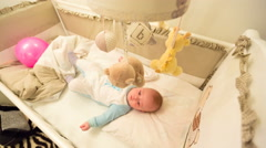 Baby lying in his cot Stock Footage