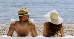 4K Happy attractive couple relaxing at the beach and running into the water Stock Footage