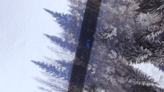 AERIAL: Blue car driving along narrow road in beautiful snowy mountain forest Stock Footage
