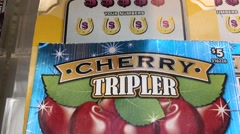 Motion of display cherry tripler lottery ticket, shot from display cabinet glass Stock Footage