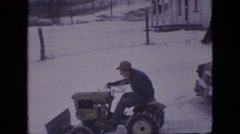 1964: through a snowy land a man drives a special truck and another man follows Stock Footage
