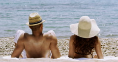 4K Happy attractive couple relaxing at the beach and running into the water.  Stock Footage