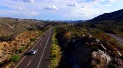 4K Aerial Crane Down Desert Highway Cars Trucks Rocks Stock Footage