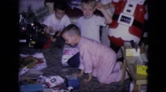 1964: children opening gifts together on christmas day, excited and jumping Stock Footage