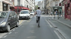 A young man does a trick while riding his skateboard in the street in Paris, Fra Stock Footage