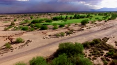 4K Aerial Drone Desert Golf Course Fly Forward Reveal Dust Storm Beyond Green Stock Footage