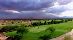4K Aerial Drone Desert Golf Course Crane Down Reveal Dust Storm Golfers Putting Stock Footage
