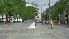 A young man does a trick while riding his skateboard down stairs in a town squar Stock Footage