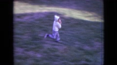 1964: young boy running outside wearing a hooded jacket, carrying a football. Stock Footage