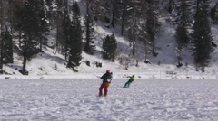 A snowkiter surfing on a frozen lake in the Switzerland Alps Stock Footage