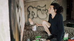 4K Young graffiti artist using different paint mediums to create artwork on wall Stock Footage
