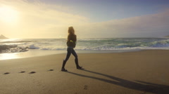 Young woman walking on beach talking on cell phone at sunset, Oregon Stock Footage