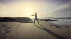 Young woman performing Tai Chi on beach at sunset, Oregon Stock Footage