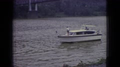 1965: a leisure boat passes several small speed boats on a river Stock Footage